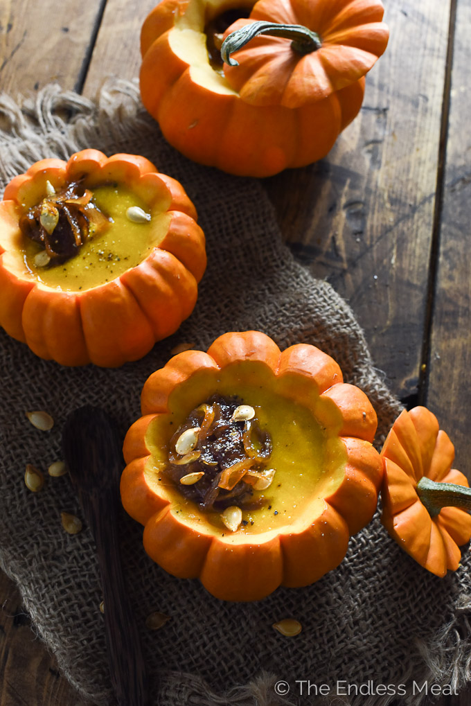 Three mini pumpkins sit on top of a piece of cloth with the tops cut off and filled with Curried Pumpkin Soup and topped with Maple Ginger Caramelized Onions, which is part of the perfect vegan comfort food recipes