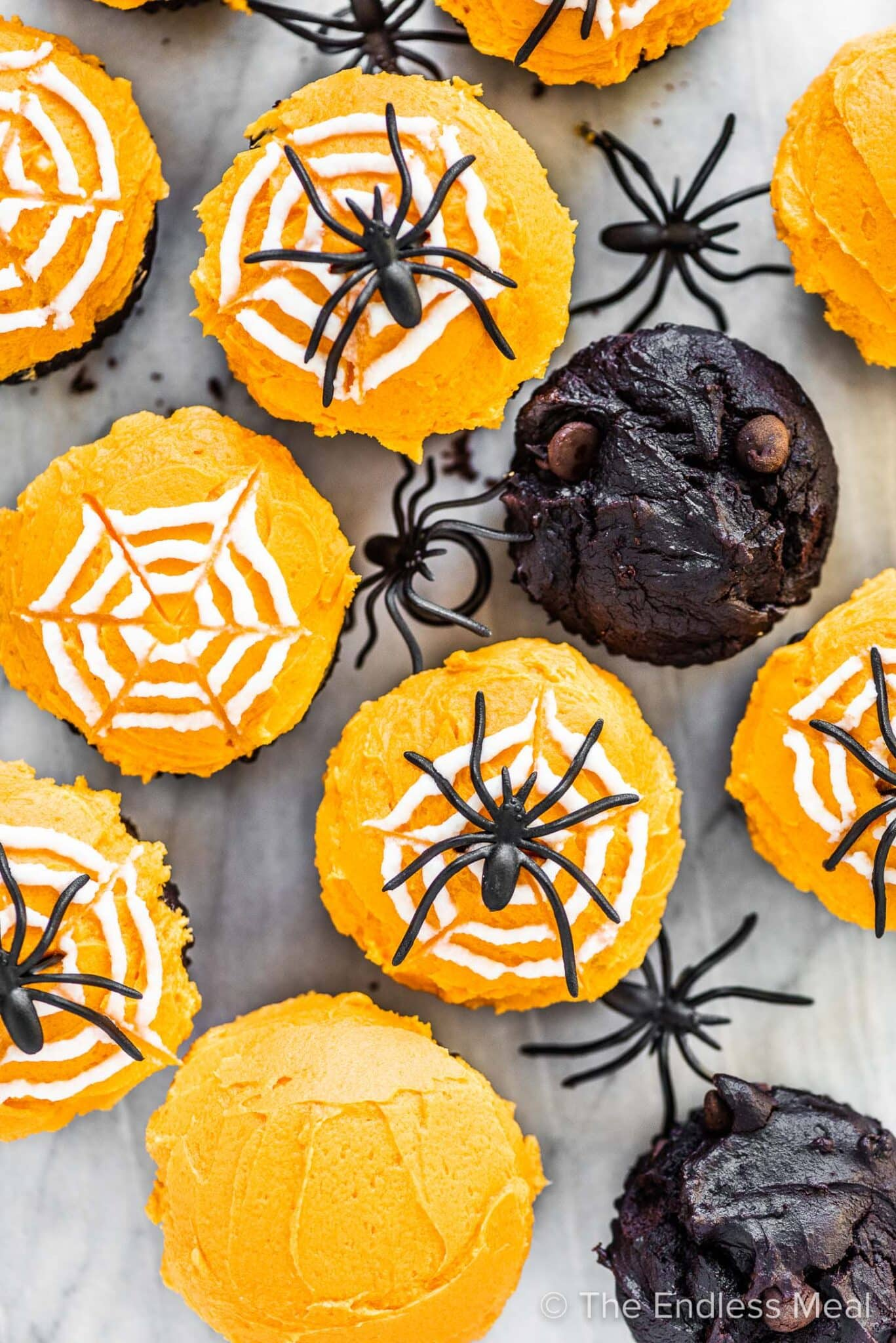 Halloween spider cupcakes on a marble background table.