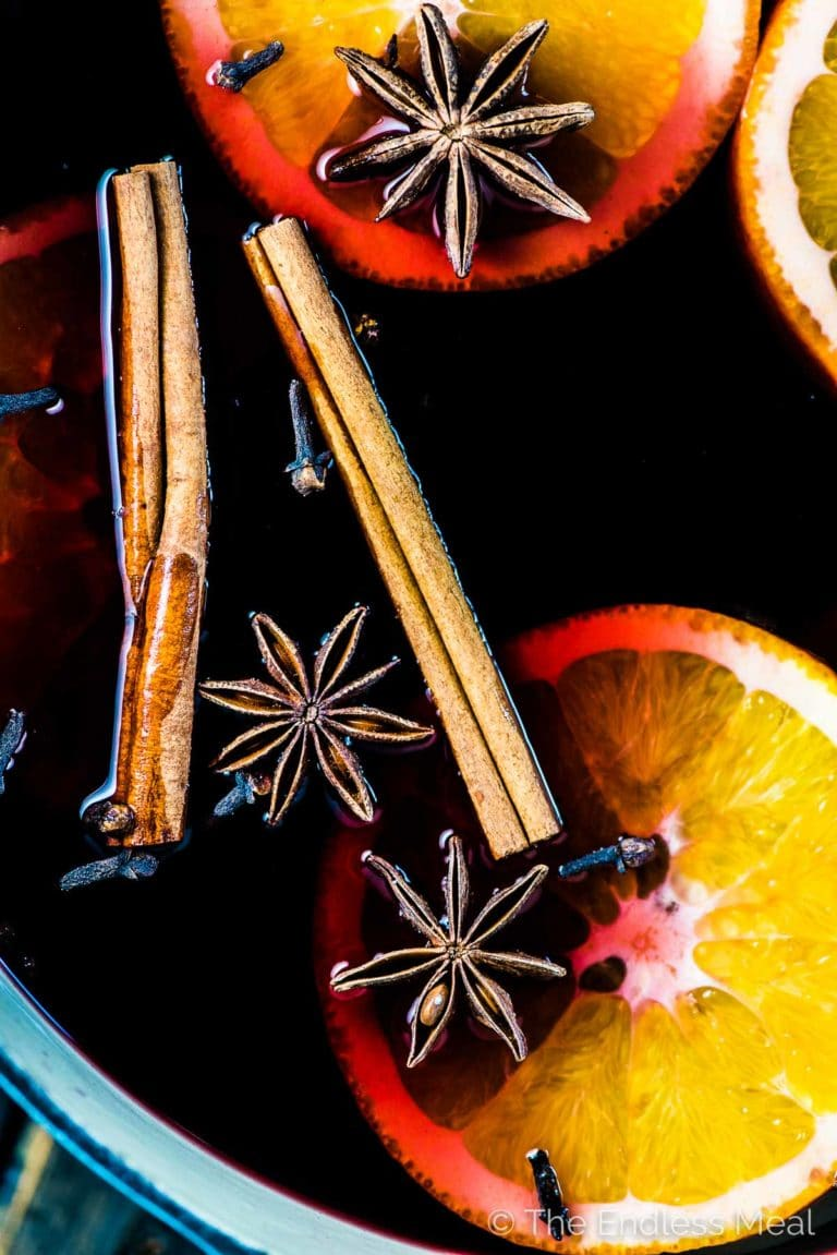 A close up of a pot of mulled wine with orange slices and mulling spices in it.
