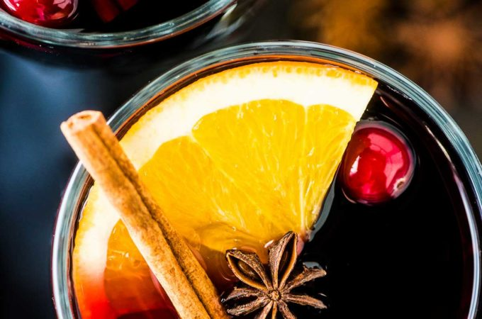 A close up of a glass of mulled wine with an orange slice, cinnamon stick, and a few cranberries in it.