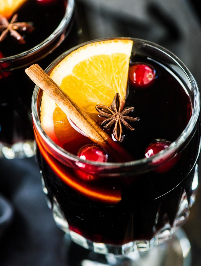 A glass of mulled wine with an orange slice, cinnamon stick, and a few cranberries in it.