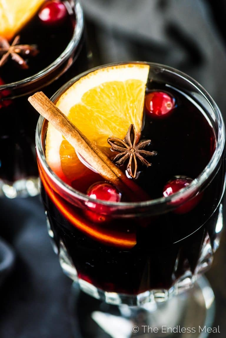 A glass of this brandy mulled wine recipe with an orange slice, cinnamon stick, and a few cranberries in it.