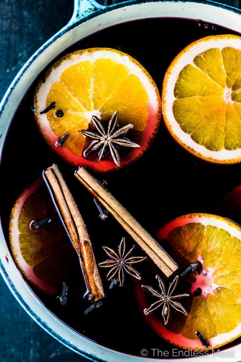 A pot of mulled wine with orange slices and mulling spices in it.