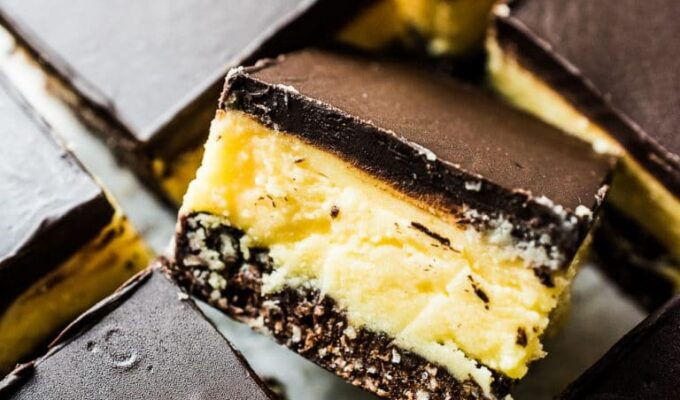Nanaimo Bars are a classic Canadian Christmas dessert. The holidays wouldn't be the same without them. This is my mom's recipe and it is less sweet than most. That's a good thing! They are made with a chocolate graham cracker, coconut, and walnut crust then topped with a layer of buttery custard and chocolate. They're amazing! | theendlessmeal.com