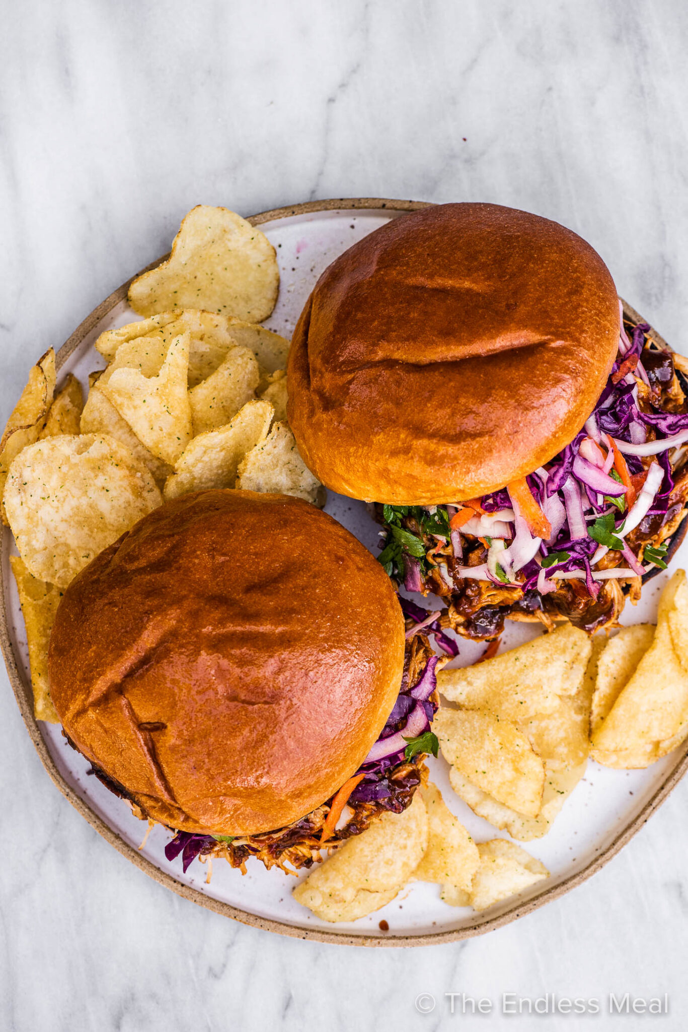 2 pulled chicken sandwiches on a plate with potato chips.
