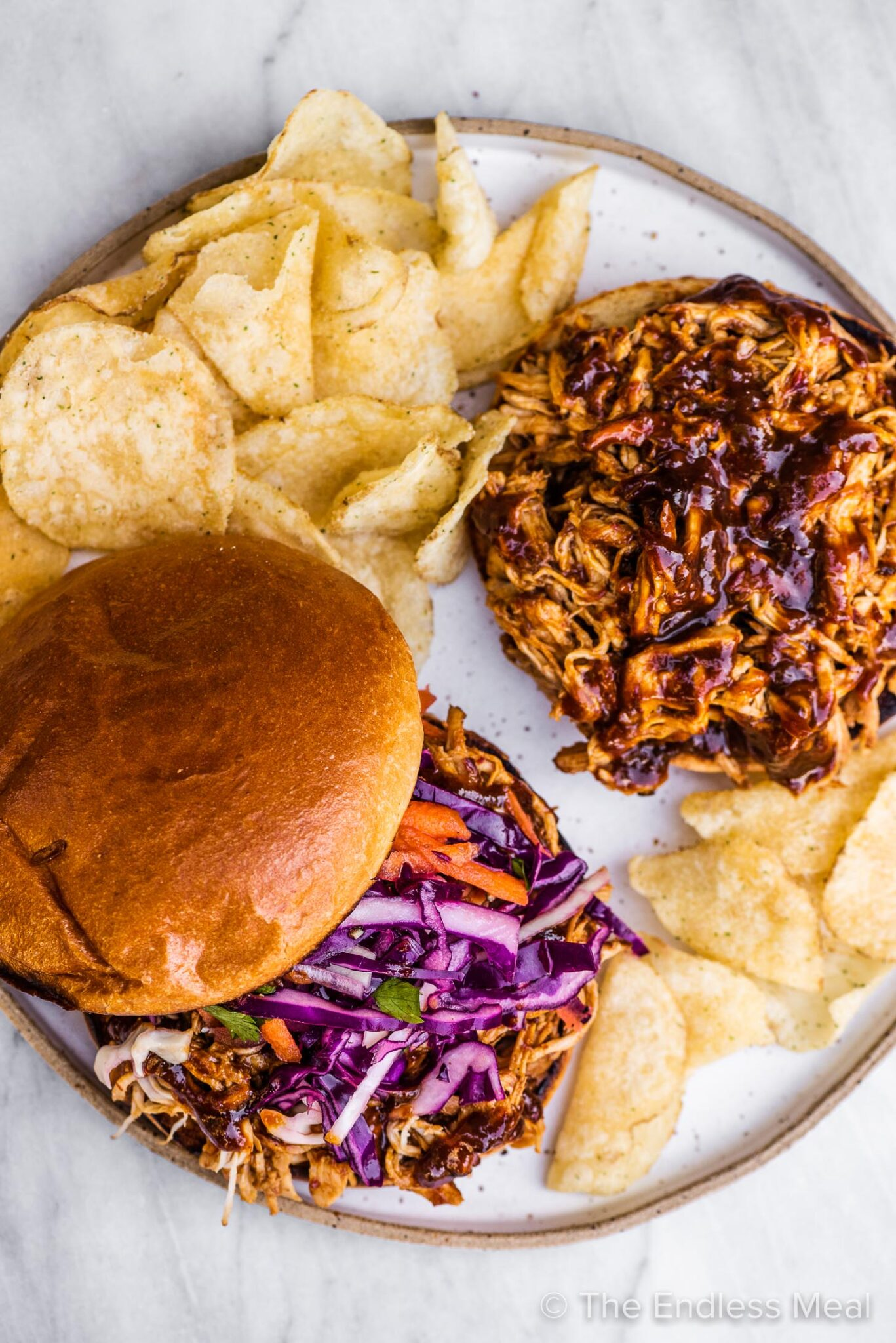 Two pulled chicken sandwiches on a plate.