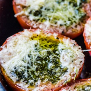 Pesto Stuffed Roasted Tomatoes are a must make side dish/ appetizer. The hollowed out tomato halves are stuffed with an easy to make, garlicky pesto them roasted until the cheese melts and the tomatoes are soft. They're delicious! | vegetarian + gluten-free + keto | #theendlessmeal #tomatoes #pesto #stuffedtomatoes #keto #glutenfree #vegetarian