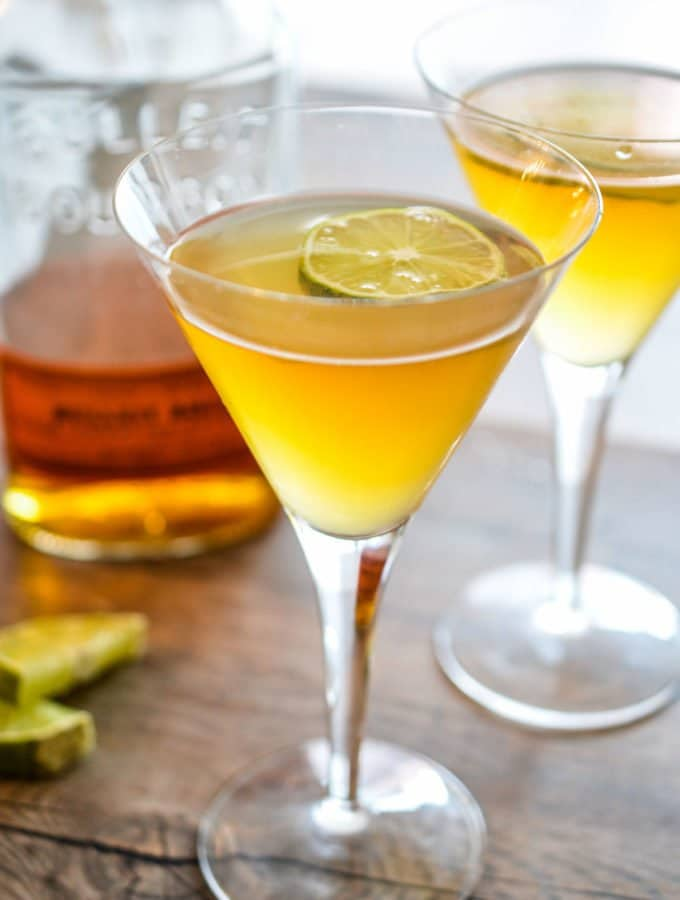 Two martini glasses filled with the best bourbon sour and a lime slice.