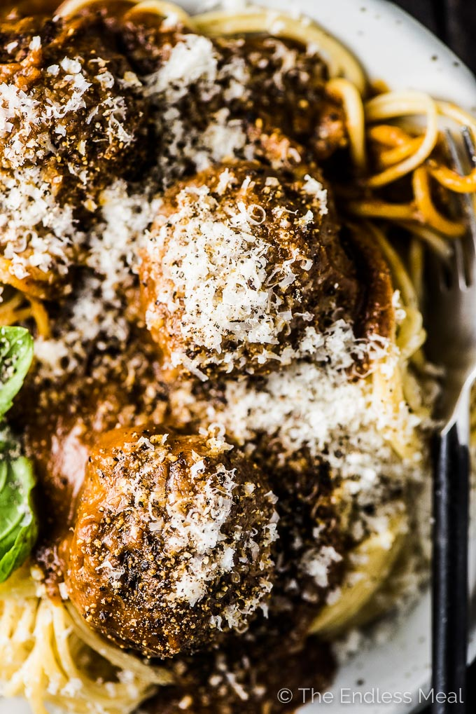 A plate of the best spaghetti and meatballs recipe with some parmesan cheese sprinkled over the top.
