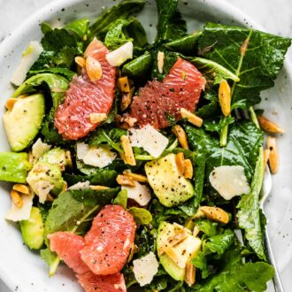 Baby kale salad on a plate with grapefruit, avocados, and almonds.