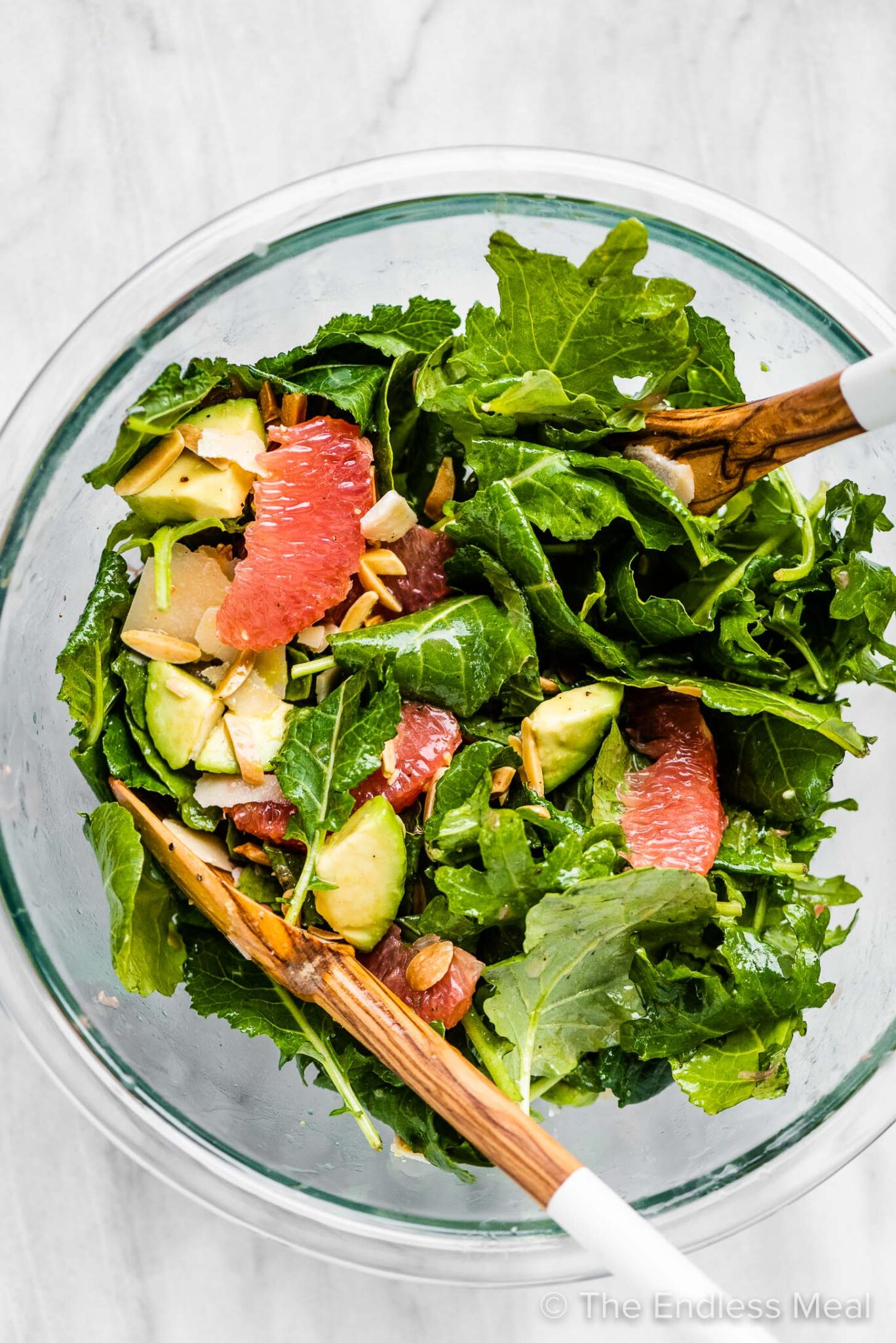 Baby kale salad in a bowl with grapefruit, avocados, and almonds.