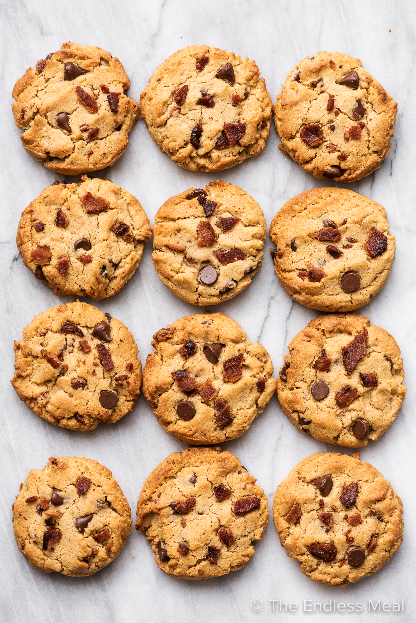 Bourbon Bacon Peanut Butter Cookies lined up on a marble counter.