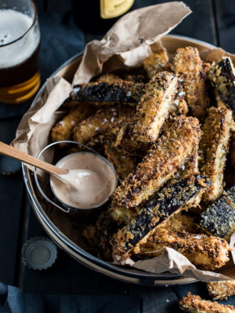 Eggplant fries piled high on a plate with a side of chipotle mayo.