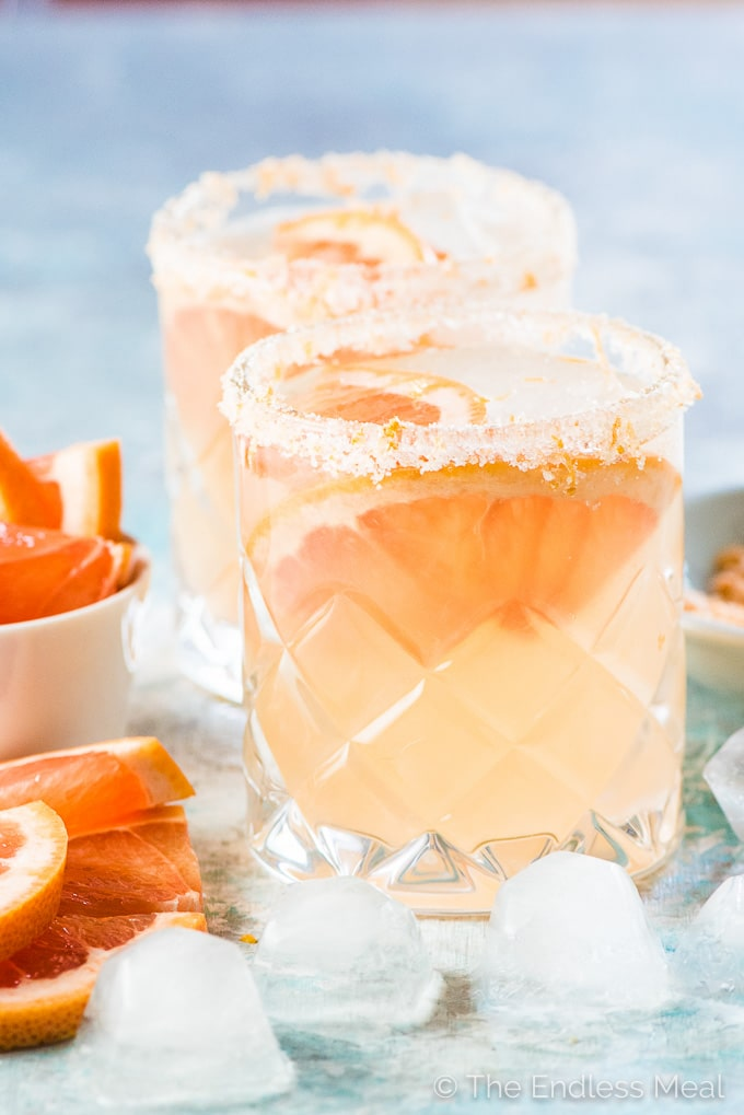 Two glasses of grapefruit margarita with slices of grapefruit and ice in glasses on a blue table