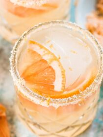 A grapefruit margarita with a slice of grapefruit and ice in a glass on a blue table
