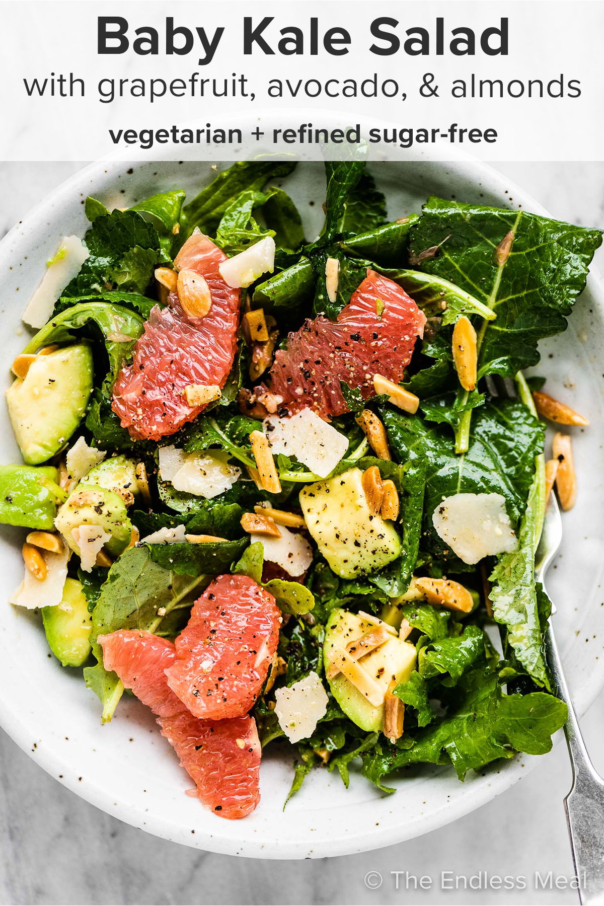 Baby kale salad on a plate with grapefruit, avocados, and almonds and the recipe title on top of the picture.