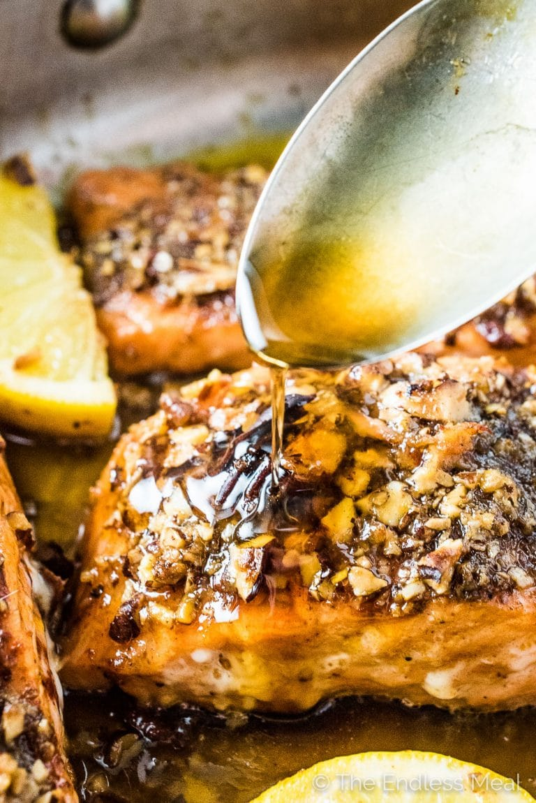 A spoon pouring the garlic maple glaze of the pecan crusted salmon.