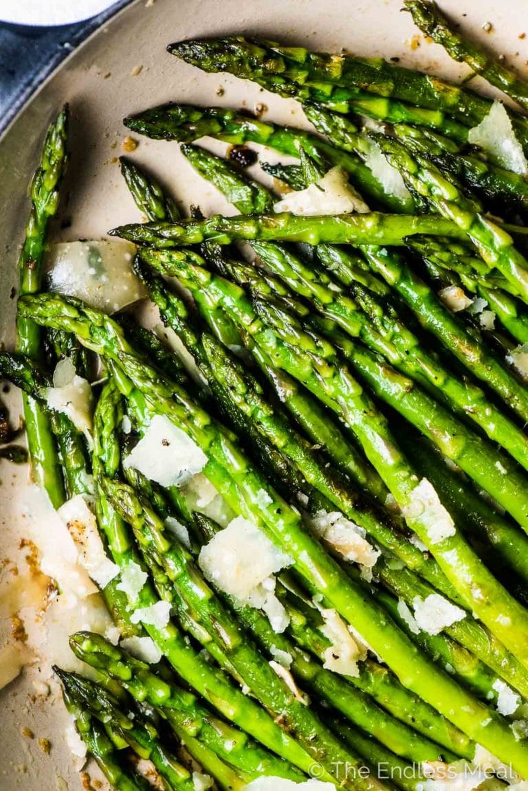 A close up of pan seared asparagus with garlic and parmesan cheese in a white pan.