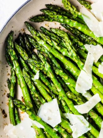 A pan of sauteed asparagus with garlic and shaved parmesan.