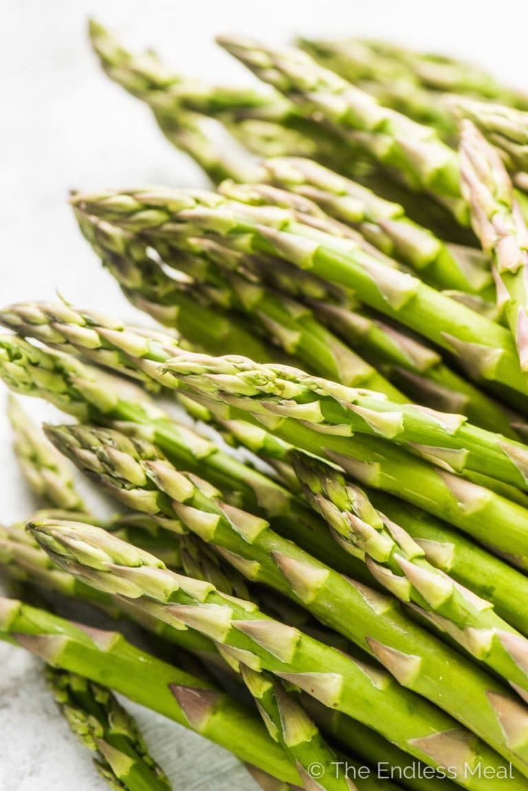 A pile of fresh asparagus ready to be turned into garlic sauteed asparagus with parmesan