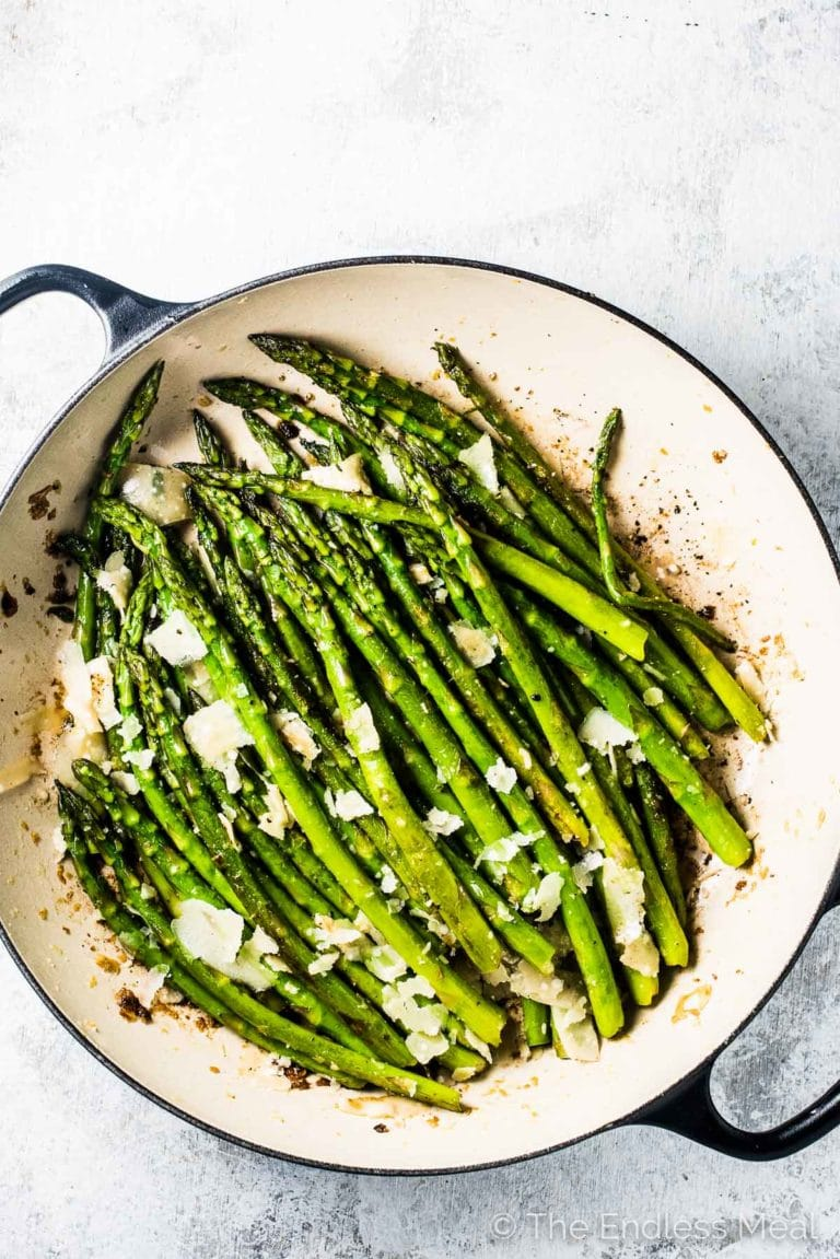 This sauteed asparagus recipe in a white pan with black handles on a white table.