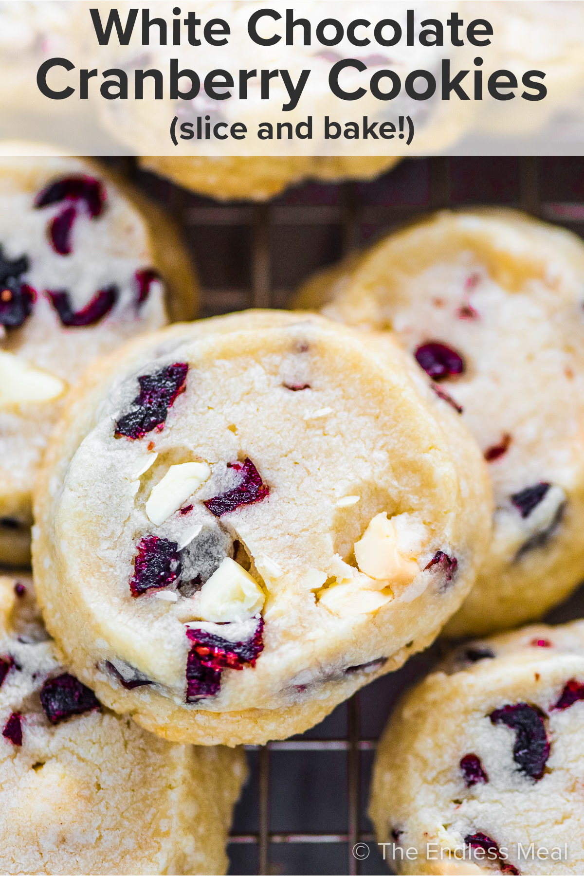 A closeup of a slice and bake white chocolate cranberry cookies with the recipe title on top of the picture.
