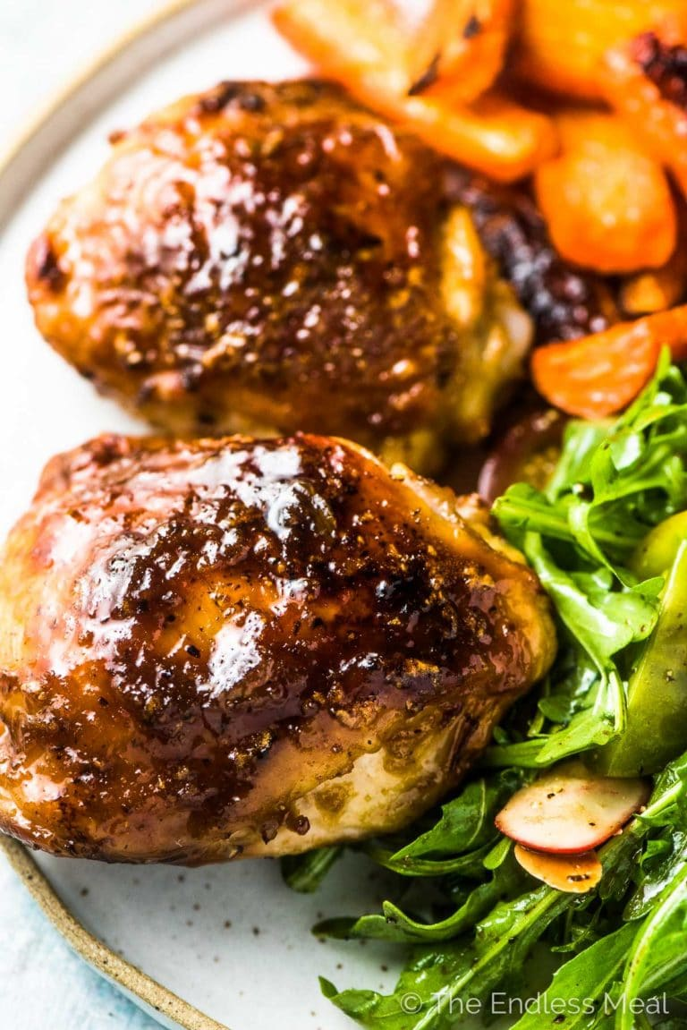 A close up of honey garlic chicken on a dinner plate with salad and carrots.