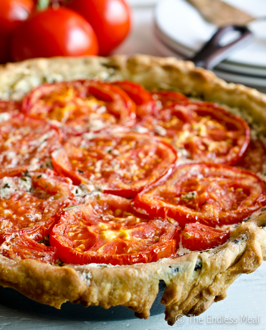 A tomato tart with bright red tomatoes and flaky crust.