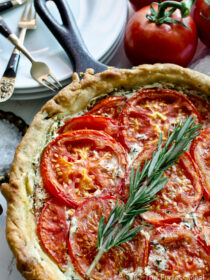 Goat cheese and Tomato Tart in a pie pan with a piece of rosemary on top.