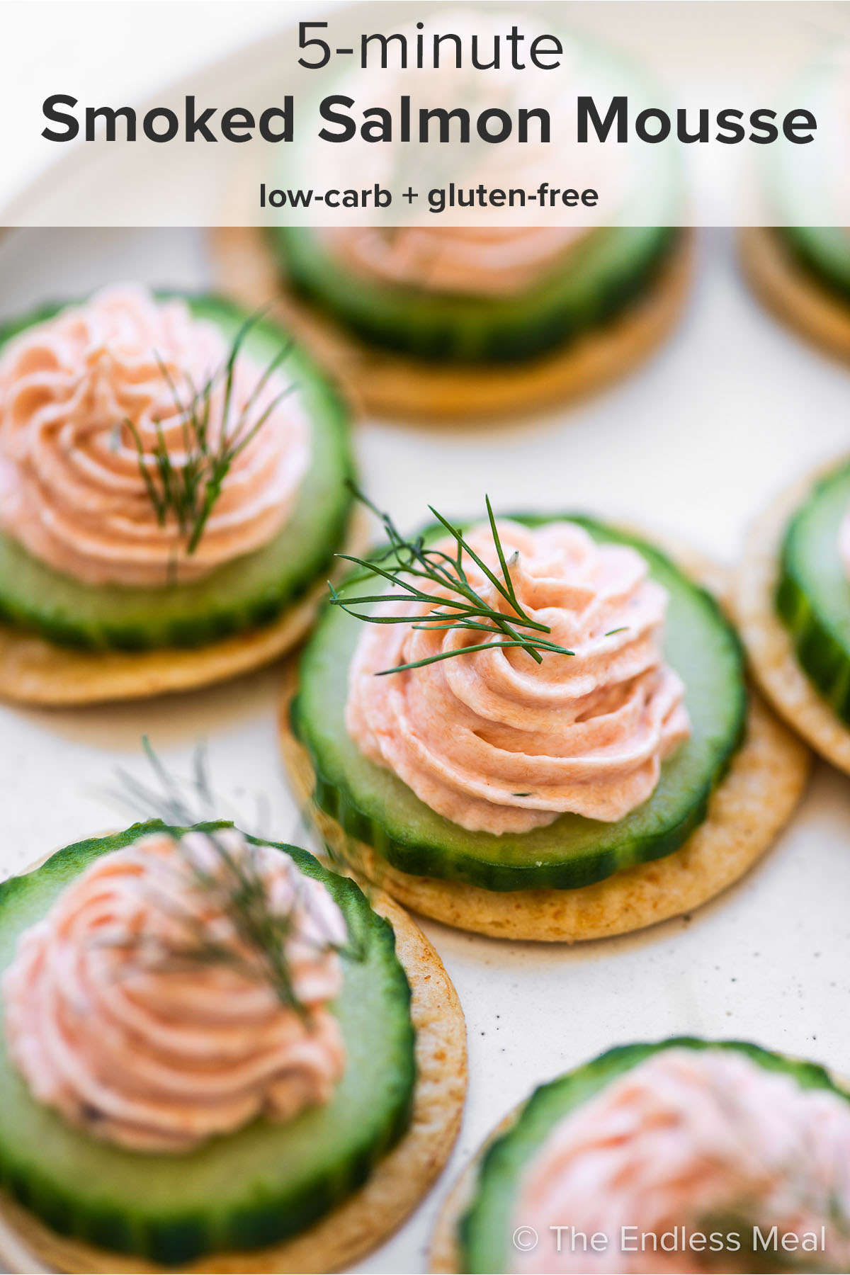 Smoked Salmon Mousse on crackers and cucumbers with the recipe title on top of the picture.