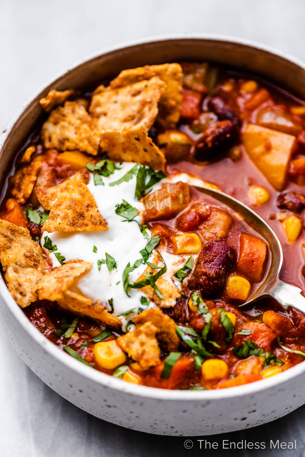 A spoon taking a scoop of this easy vegetarian chili recipe from a white bowl.