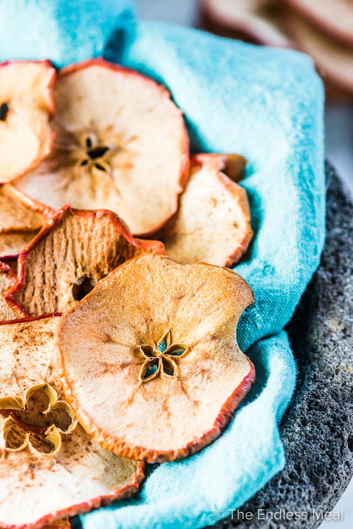 Crispy baked apple chips on a blue cloth.