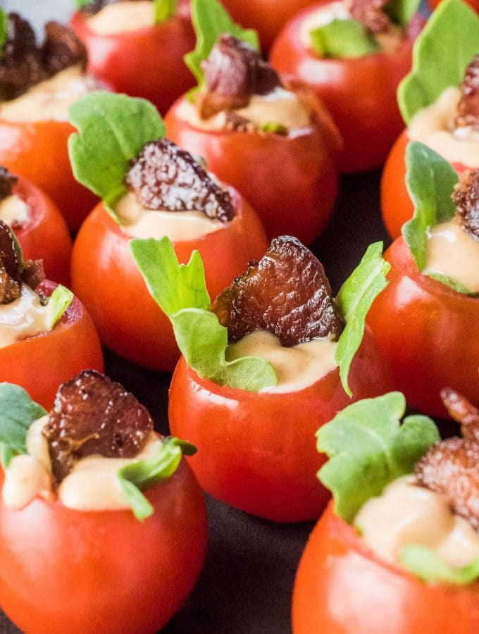 If you're looking for bite-sized appetizers for your next party, look no further. These Mini BLT Cups are as cute as they are delicious! Cherry tomatoes are stuffed with arugula and a little chipotle mayo then topped with a piece of crunchy bacon. They're a healthy gluten-free + paleo + Whole30 appetizer recipe that everyone will love!