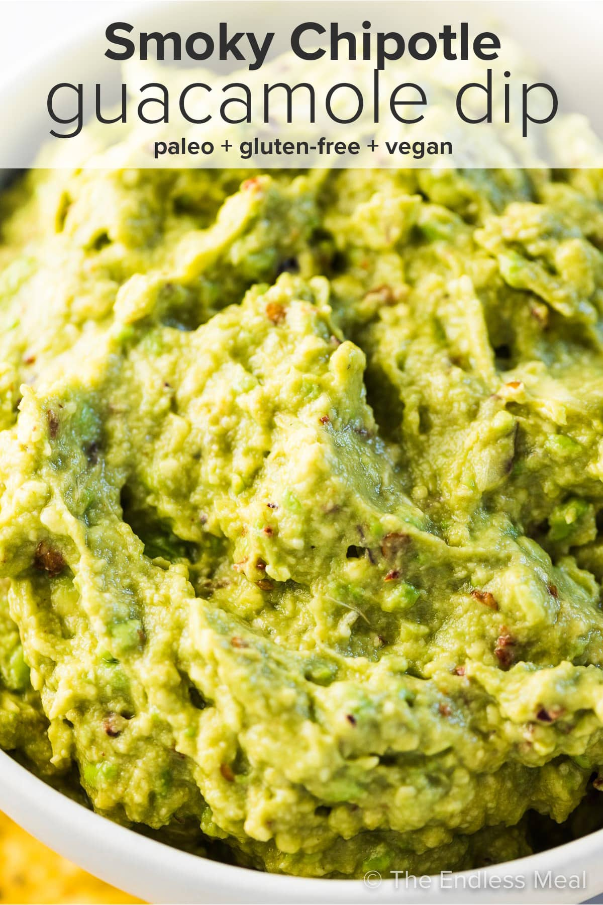 A close up of smoky chipotle guacamole dip with the recipe title on top of the picture.