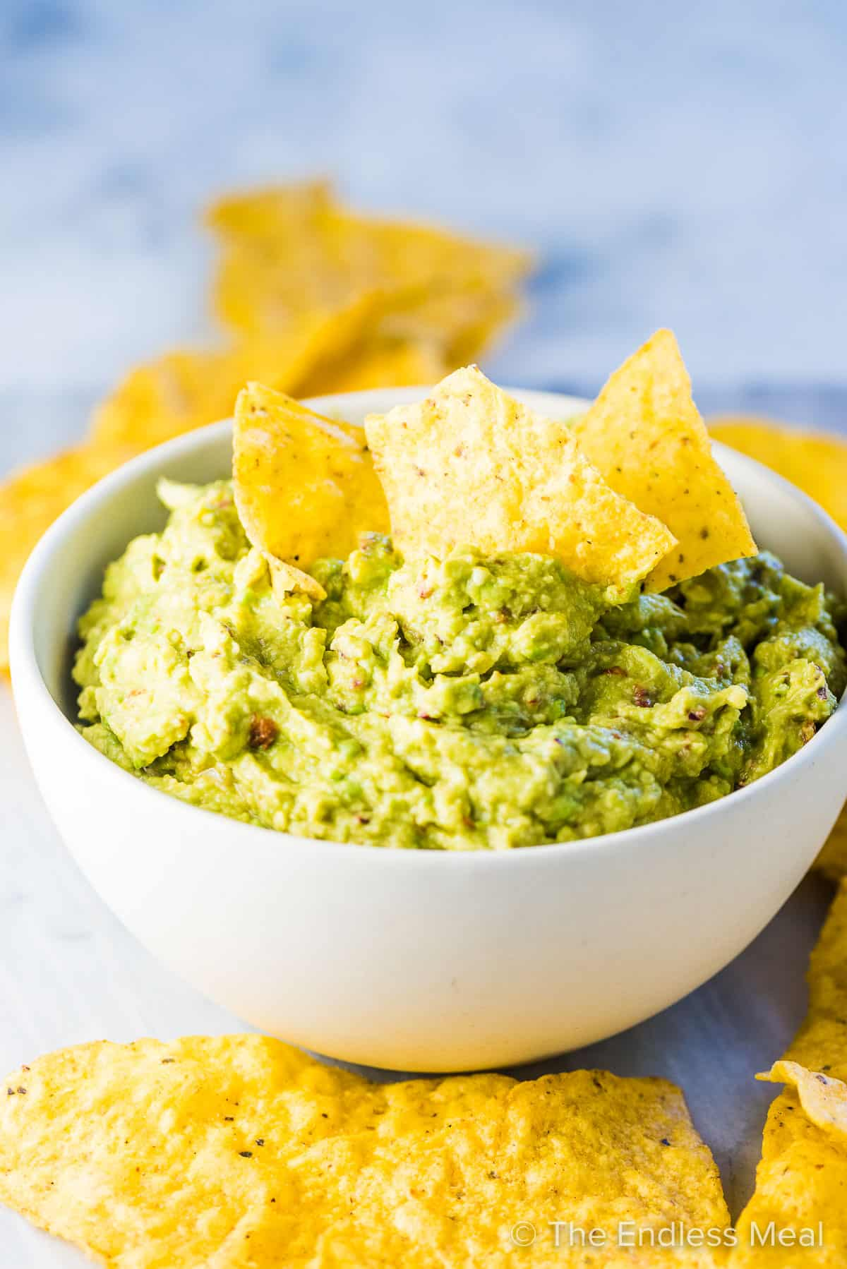 Chipotle guacamole dip in a white bowl with tortilla chips on top.