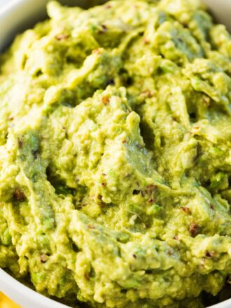 A close up of chipotle guacamole in white bowl.