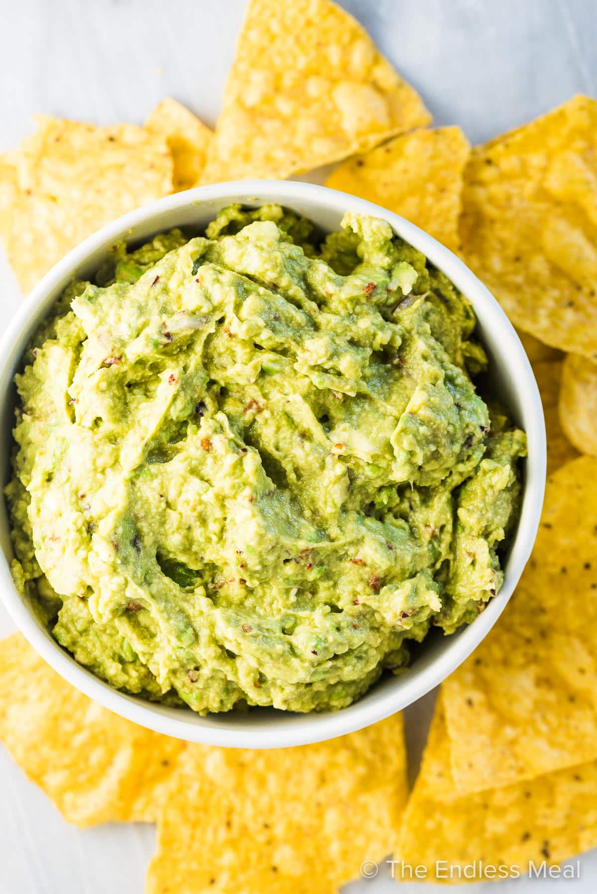 Looking down on a bowl of chipotle guacamole dip surrounded by yellow corn chips.