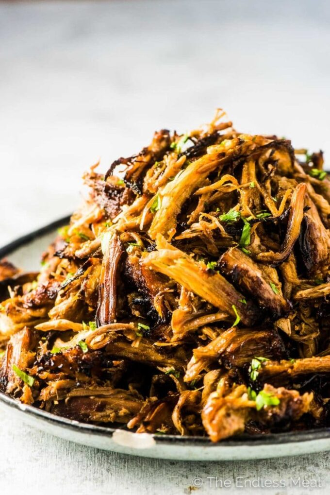 A big pile of Mexican pork carnitas on a plate.