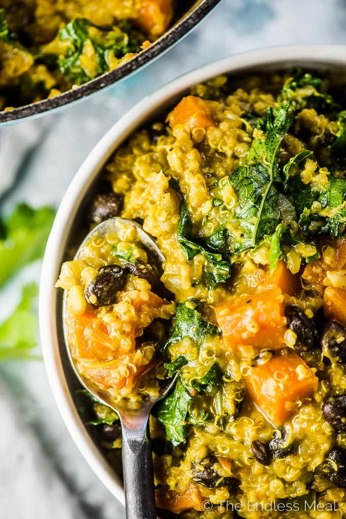 A spoon in a bowl of Curried Quinoa Vegetable Stew.