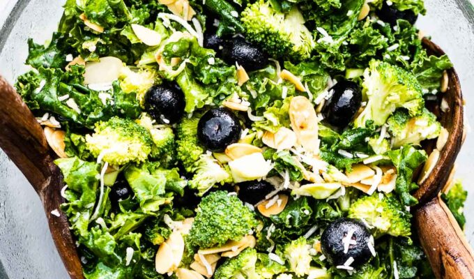 Broccoli Kale Salad with Blueberries and Coconut in a glass salad bowl with wooden tongs