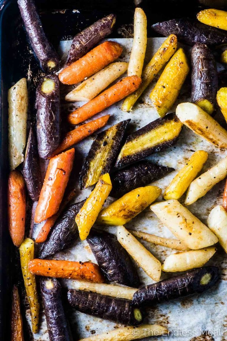 Multi colored oven roasted carrots on a baking sheet ready to be tossed with carrot top pesto.