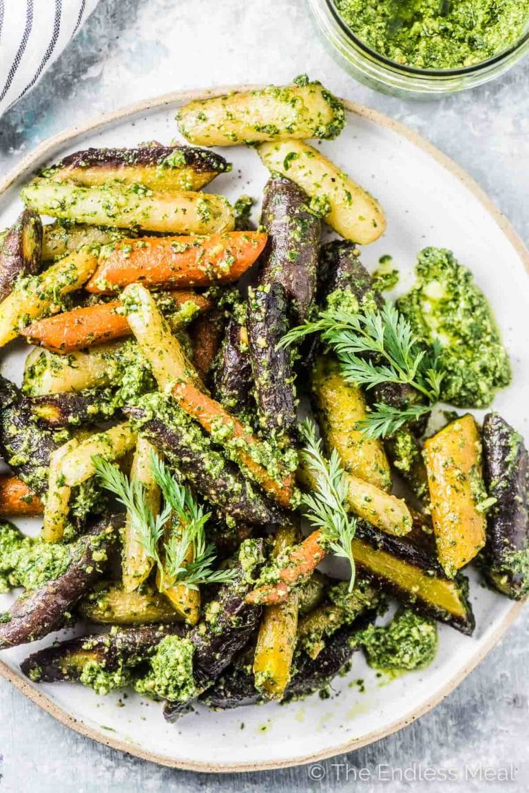 Oven roasted carrots tossed in carrot top pesto on a serving plate.