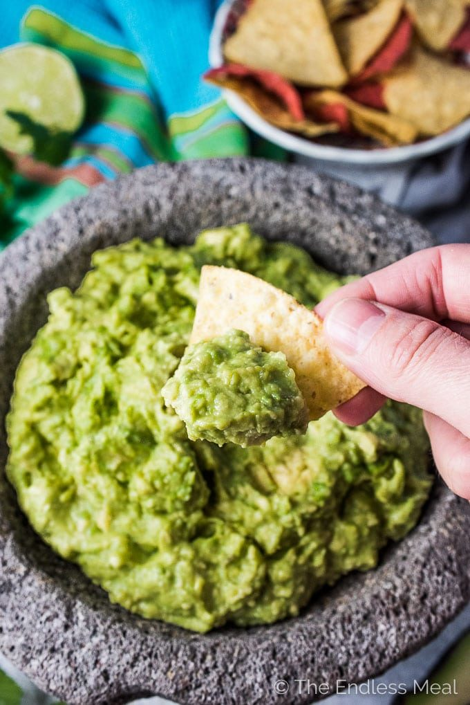 A tortilla chip scooping some guacamole out of a serving dish.