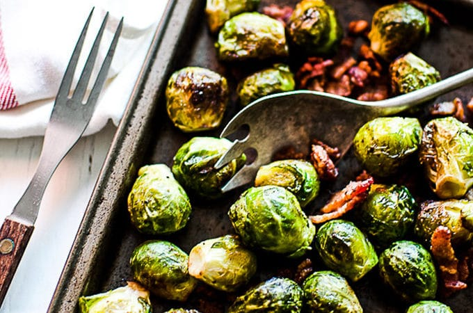 A tray of bacon roasted brussels sprouts with a serving spoon it in.