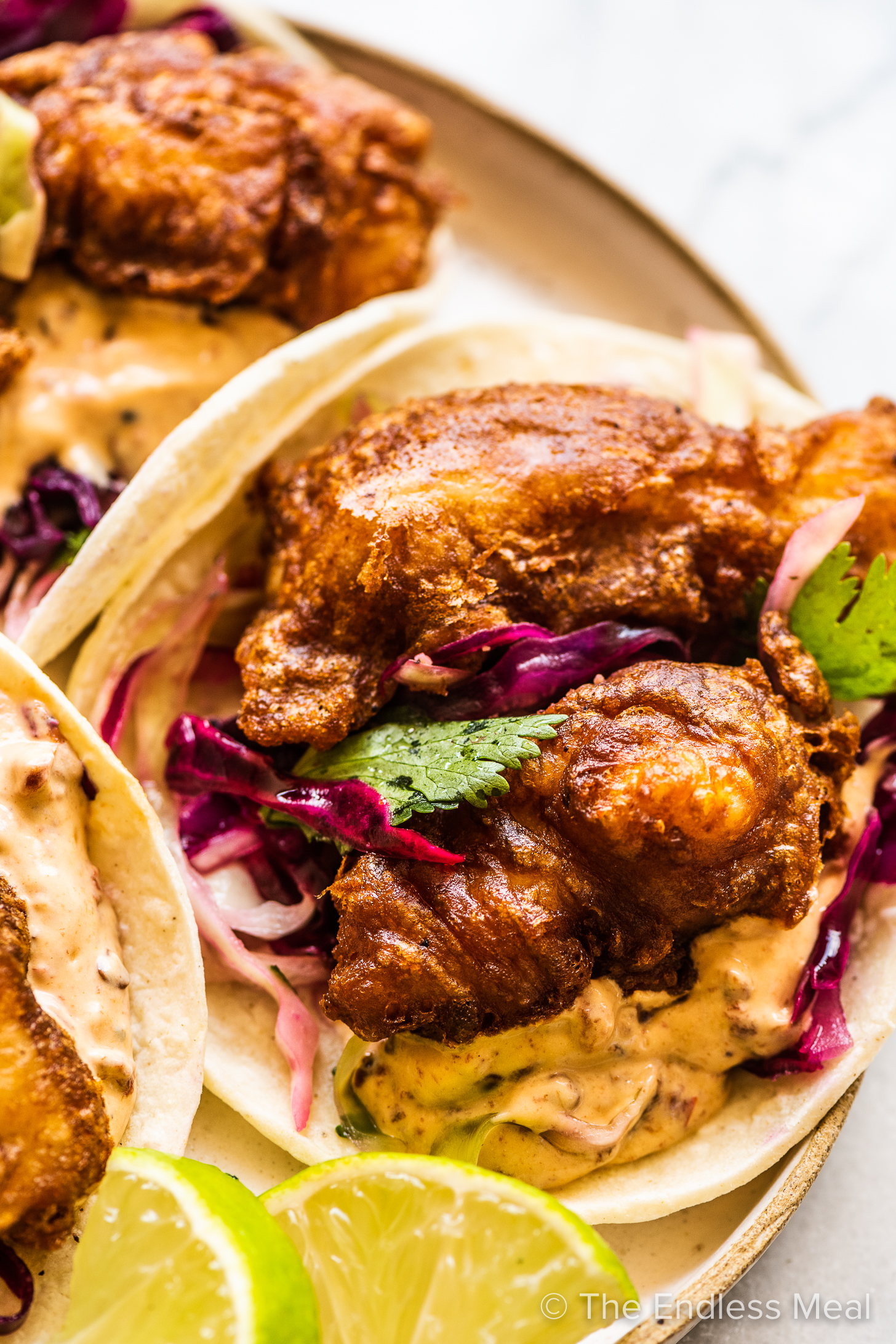 Beer Battered Fish Tacos on a white plate.