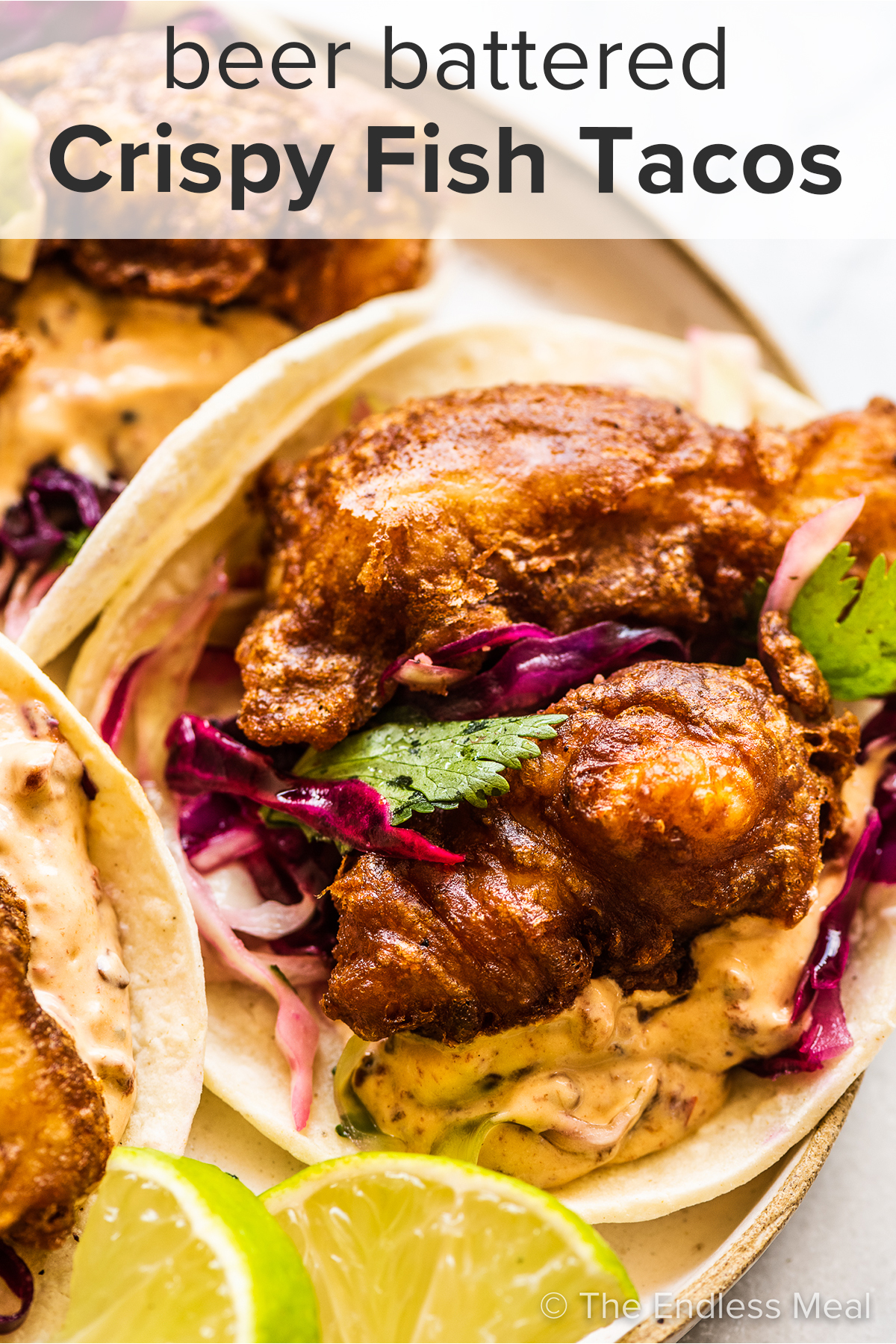 Beer Battered Fish Tacos on a white plate with the recipe title on top of the picture.