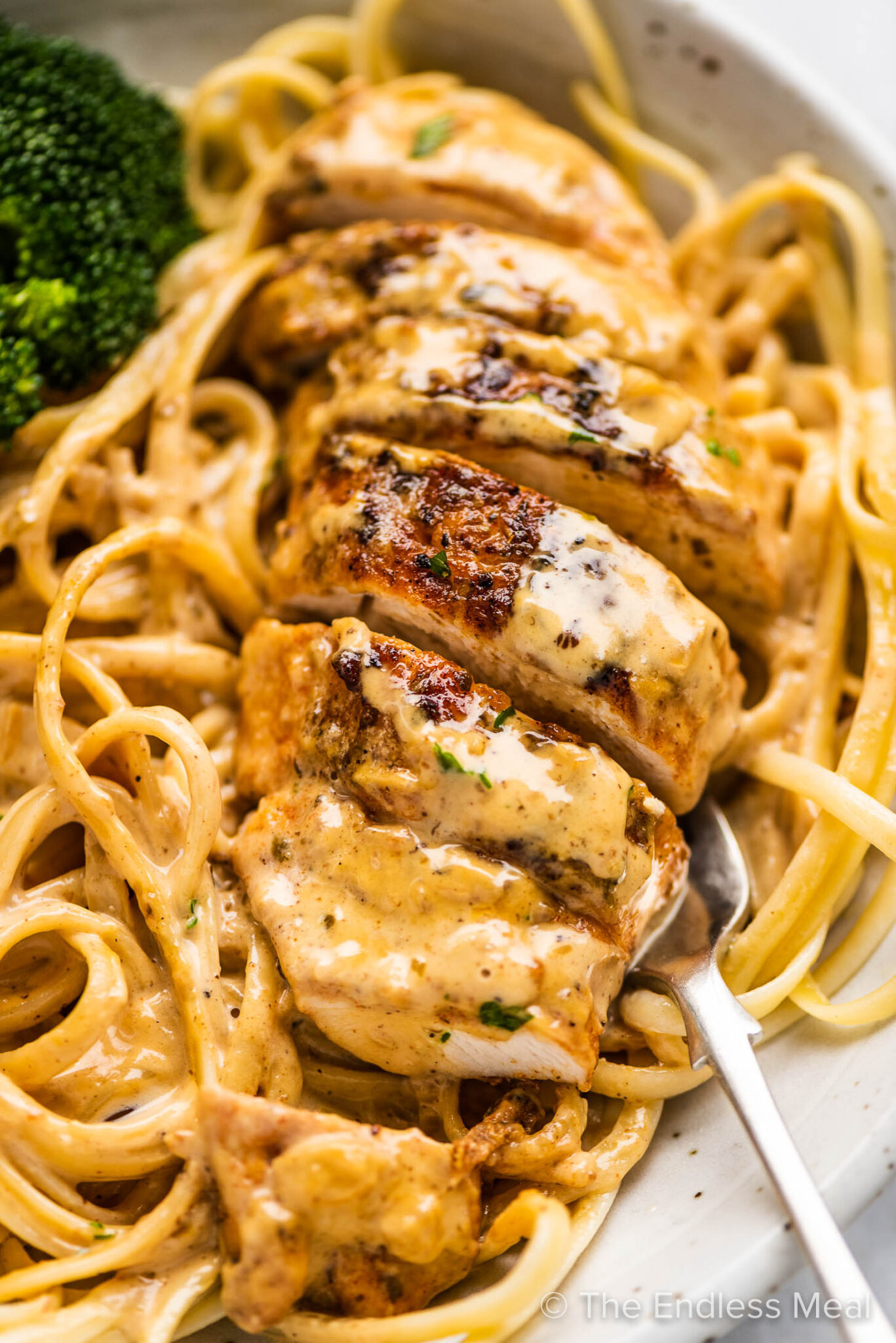 A close up of chicken lazone pasta on a white plate with a side of broccoli.