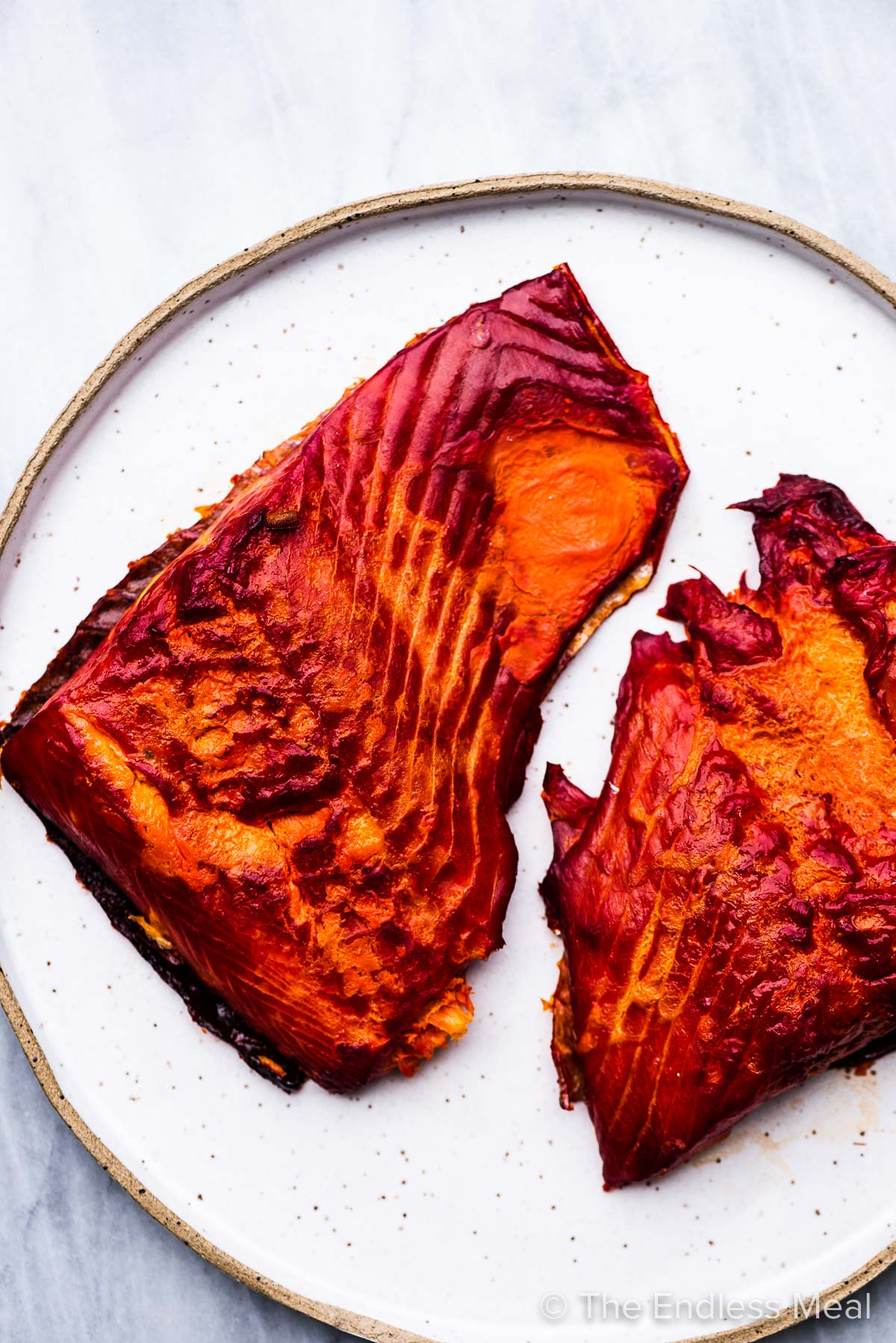Two pieces of hot smoked salmon on a white plate.