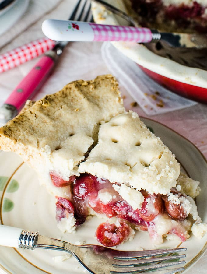 A pie of homemade fresh cherry pie on a plate with pink and red cutlery and the rest of the pie in the pie pan beside it.
