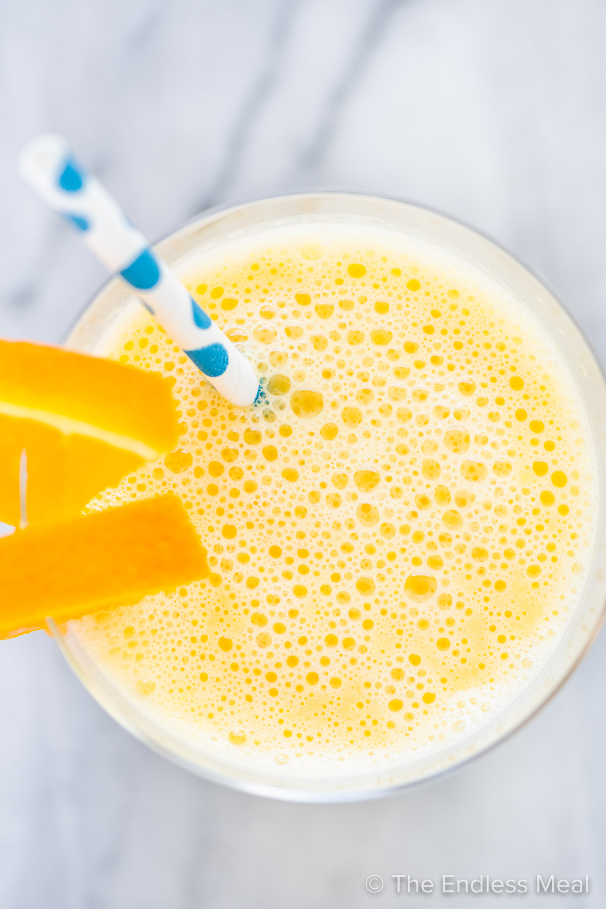 Looking down on an orange smoothie with a blue straw and orange slices.